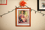 December 16, 2010. Raleigh, NC.. Family photos are mixed in with religious iconography on the wall of TP Mishra's apartment. . TP Mishra, a refugee from Bhutan, has recently relocated from the Bronx to Raleigh, where he lives in an suburban apartment  with his wife, as well as another Bhutanese couple.