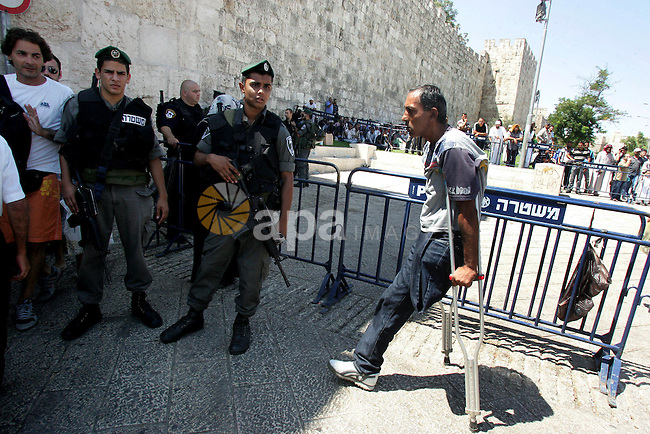 Israeli border policemen keep watch as Palestinian Muslim worshipers perform the third Friday prayer of Islam's holy month of Ramadan outside Damascus Gate in Jerusalem's Old City on August 19, 2011.  Photo by Mahfouz Abu Turk