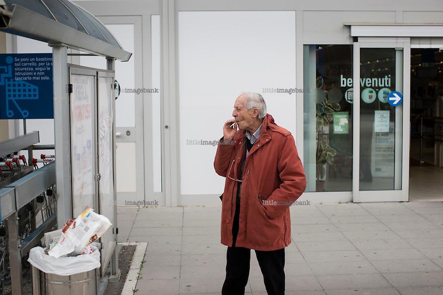 L'aquila, Abruzzo, Italia. 26.03.2014. En mann nyter sin sigarett utenfor et kjøpesenter ved Onna. L'aquila, 6. april 2009 kl. 03:32: Et jordskjelv som måler 6.3 ryster byen. 309 mennesker mister livet. Fem år senere sliter de som overlevde fortsatt med etterskjelvene, i form av en guffen cocktail av uærlige offentlige tjenestemenn, mafia og 494 millioner øremerkede euro på avveie. Fotografier til bruk i feature i DN lørdag 05.04.2014. Foto: Christopher Olssøn.