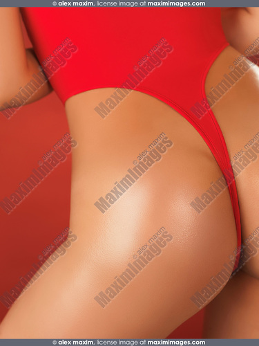 Sexy young woman with shiny tanned body wearing high-cut double dip swimsuit closeup of back