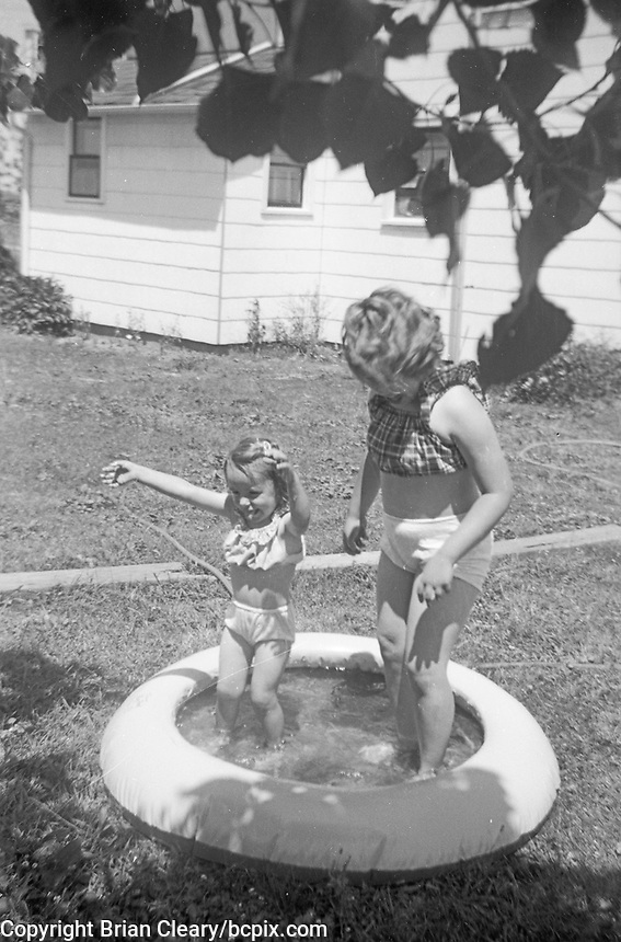 Two young girls play in a backyard wading pool during the 1940's.   (Photo by bcpix.com)