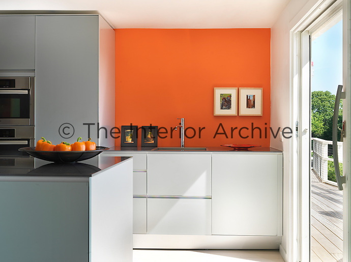 The contemporary kitchen has a vibrant orange wall behind the sink