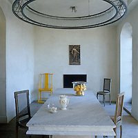 A round metal-framed chandelier designed by Carl Vercauteren hangs above the long marble table in the dining room
