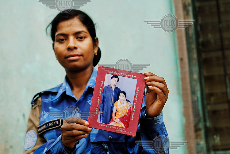 LIBERIA, Monrovia, 13/04/2007..Vaishali holds up a photograph taken on the anniversary of her wedding day. Her husband, Abhijeet Shembekar, is an engineer. Like many of the unit's women her marriage was arranged by her parents...© 2007 Aubrey Wade. All rights reserved.