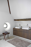 Double basins supported by a wooden washstand are illuminated by a porthole window in this double-height attic bathroom