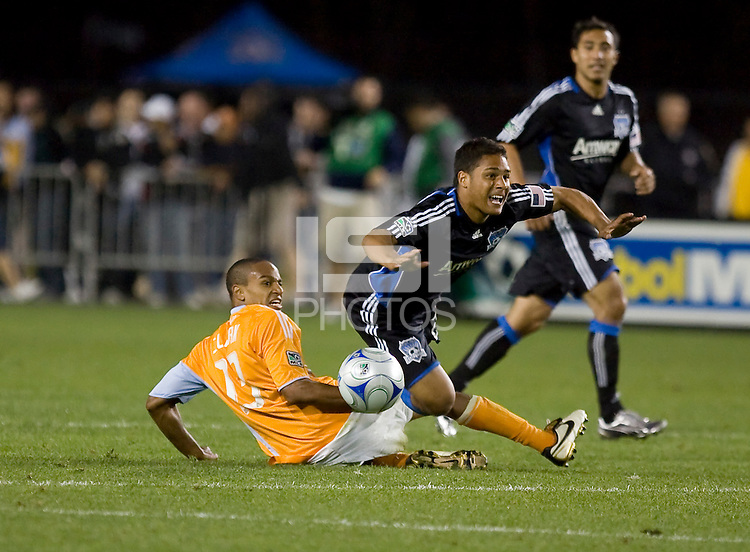 Ricardo Clark (13) slides tackles Quincy Amarikwa (right). San Jose Earthquakes defeated Houston Dynamo 3-2 at Buck Shaw Stadium in Santa Clara, California on March 28th, 2009.