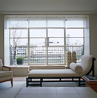 The daybed is positioned to take full advantage of the rooftop view of London through the French windows