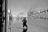An anti-Gaddafi fighter wades through flooded battle-torn street in Sirte, Libya.