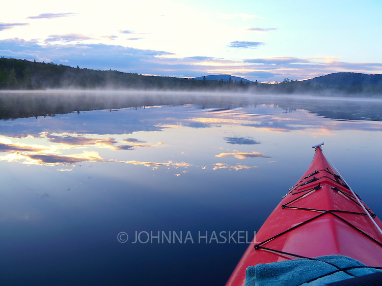 Sunrise is a magical time to kayak on Rangeley Lake with the smooth water showing the reflection of the early morning clouds.