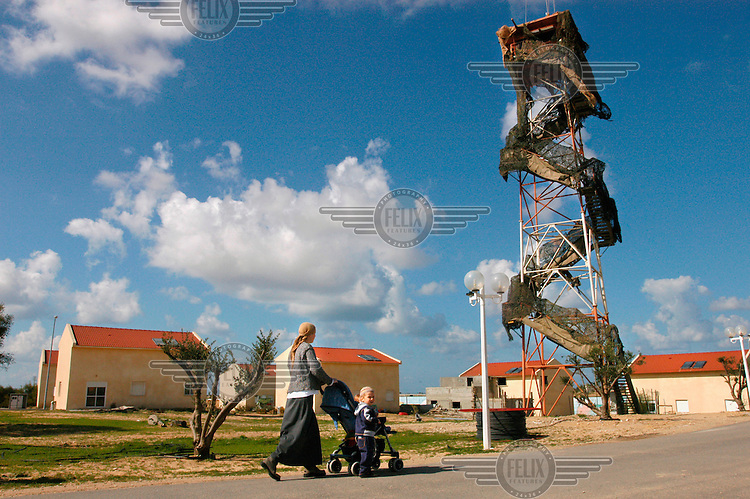 A mother takes a walk with her baby past an Israeli army watch tower in the Gaza Strip Jewish settlement of Morag. Israeli prime minister Ariel Sharon wants to withdraw from the Gaza Strip which would result in all settlers being evicted.