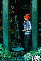 Young boy shopkeeper in a fruit and vegetables shop in Patan, Nepal.  He has old-fashioned scales for weighing the produce.