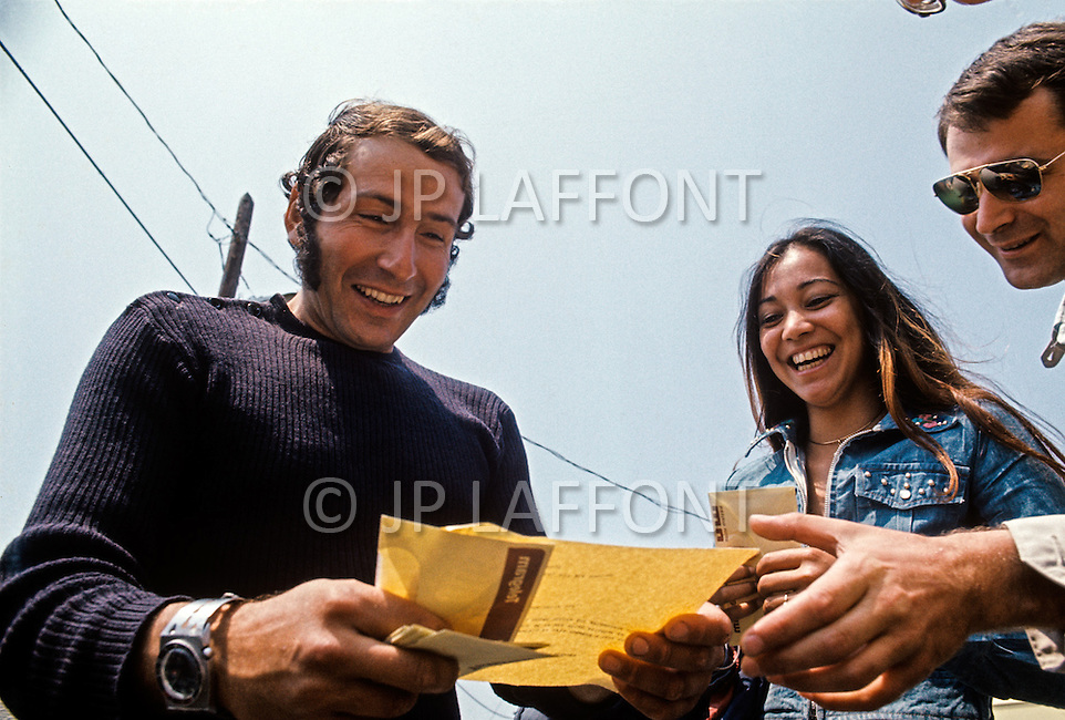 Newport RI, US - July 7, 1972. French navigator Alain Colas with wife Teura Krause, and friends after winning the 1972 Transat Plymouth-Newport race. Alain Colas (September 16, 1943 - November 16, 1978) was the first sailor to complete a solitary round the world race in a multihull and endeavored to complete the 1978 Route du Rhum, however disappeared in the Atlantic after passing Azores.