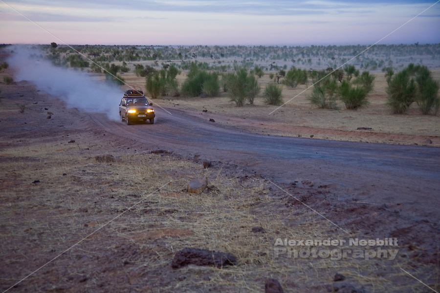 Mali, 2009 - A Land Cruiser drives across the  rugged dirt track in the vast best open stretch of northern Mali between Timbuktu and Douentza at dusk.
