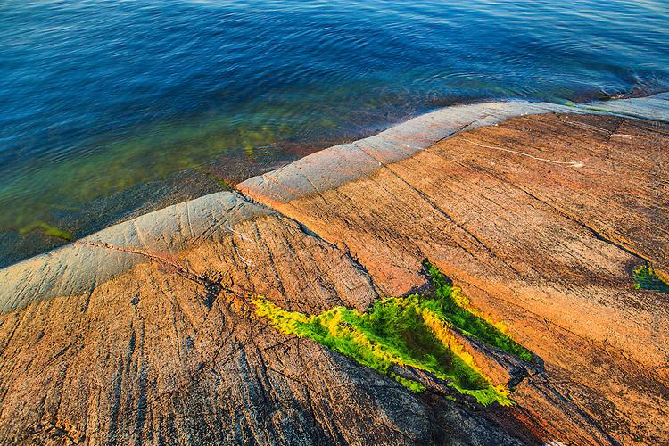 Solbelyst häll i varmt kvällsljus vid Furusund Roslagen Stockholms skärgård. / Sunlit rock in warm evening light at Furusund Roslagen Stockholm archipelago.