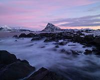 Offersøykammen mountain peak rises into the twilight of the Acrtic Polar Night from Storsandnes beach, Flakstadøy, Lofoten Islands, Norway