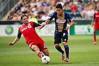 Torsten Frings (22) of Toronto FC goes for a tackle on Roger Torres (8) of the Philadelphia Union. The Philadelphia Union defeated Toronto FC 3-0 during a Major League Soccer (MLS) match at PPL Park in Chester, PA, on July 8, 2012.