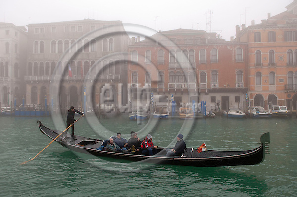 Venice-Italy - January 16, 2011 -- A gondoliere / gondolier on tour with tourists on Grand Canal / Canal Grande in the early morning winter mist, gondola -- tourism, infrastructure, transport, water -- Photo: Horst Wagner / eup-images