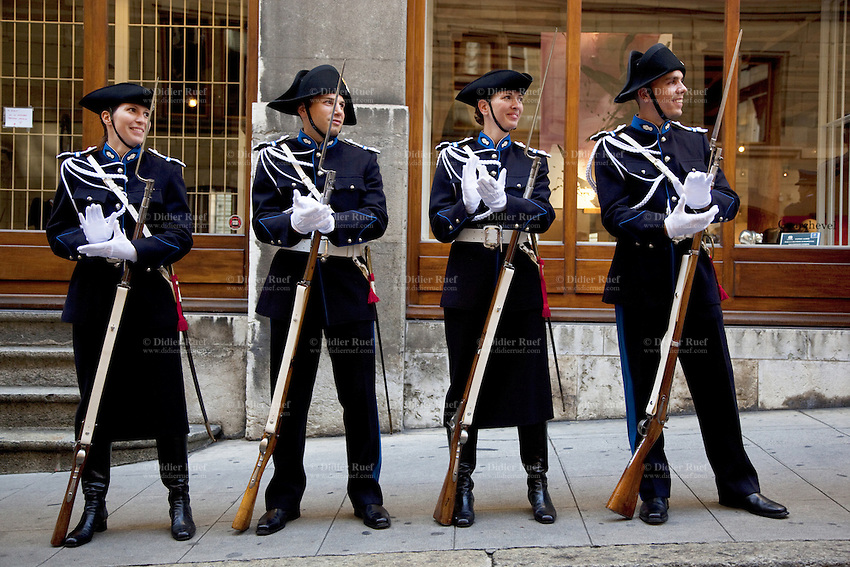 Switzerland. Geneva. Old town. A group of recruits (policemen and policewomen) from the police academy smile and applaud on the day in which they will be all sworn in as police officers. They wear uniforms, white gloves, tricorns on the heads and carry old rifles with bayonet. The tricorne or tricorn is a style of hat that was popular during the 18th century, falling out of style by 1800. The tricorne was worn as part of military uniforms. A bayonet (from French ba?onnette) is a knife, sword, or spike-shaped weapon designed to fit in, on, over or underneath the muzzle of a rifle, effectively turning the gun into a spear. 29.08.12 © 2012 Didier Ruef...