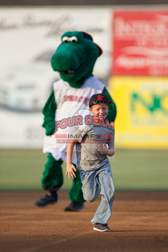 A young fan races Kannapolis Intimidators mascot Tim E. Gator around the bases between innings of the South Atlantic League game against the Asheville Tourists at Kannapolis Intimidators Stadium on May 26, 2016 in Kannapolis, North Carolina.  The Tourists defeated the Intimidators 9-6 in 11 innings.  (Brian Westerholt/Four Seam Images)