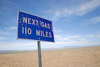 4415 / Kult State Route 375: AMERIKA, VEREINIGTE STAATEN VON AMERIKA, NEVADA,  (AMERICA, UNITED STATES OF AMERICA), 25.07.2006: Strassenschild Next Gas 110 Miles. Lange fahrtstrecke bis zur naechsten Tankstelle, Benzinversorgung,  Die Nevada State Route 375, besser bekannt als Extraterrestrial Highway (seit 1996 offiz. Bezeichnung), Highway 375 oder kurz ET-Highway, ist eine Bundesstrasse in den Counties Lincoln und Nye im Sueden Nevadas im Suedwesten der USA. Sie verlaeuft zwischen Warm Springs, wo sie vom U.S. Highway 6 abbiegt und Crystal Springs, wo sie ueber eine kurzen Abstecher auf die Nevada State Route 318 in den U.S. Highway 93 einbiegt, und ist 158 Kilometer (98,4 Meilen) lang. Einziger und ebenfalls beruehmter Ort entlang der Strasse ist Rachel, wo viele der wenigen Durchreisenden im Little A'Le'Inn, einer mit UFO-Devotionalien dekorierten Bar, einen kurzen Halt einlegen...