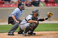 Home plate umpire Gerard Ascani sets up behind catcher Chris Hatcher #36 of the Jacksonville Suns at Five County Stadium May 16, 2010, in Zebulon, North Carolina.  Photo by Brian Westerholt /  Seam Images
