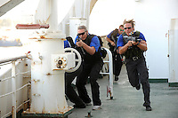 John Skovbo (centre), from Denmark, with his team mates, takes part in a training course to fight maritime terror and piracy, on a boat in Haifa Port...