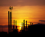 Chimneys silhouetted against the sun setting at chemical plant. Teeside, Cleveland, England.