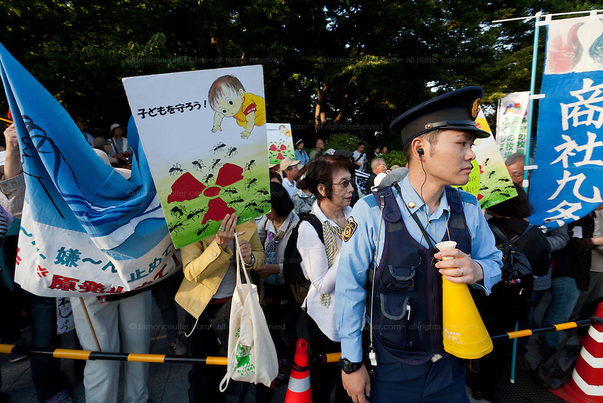 A policeman controls crowds at an anti nuclear protest around the National Diet Building in Kasumigaseki, Tokyo, Japan Sunday June 2nd 2013