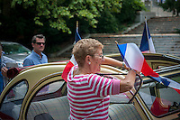 Wendy Batreson affixes French flags to her Citroen 2CV prior to the Greater New York Citorën and Velosolex Touring Club parade of their lovingly restored Citroën automobiles during their Bastille Day Rendez-Vous, seen on Riverside Drive in New York on Sunday, July 14, 2013. The parade of over a dozen Citroëns, including 2CV, DB series models, a truck and a traction avant started on Riverside Drive and traveled through the streets of Manhattan. The owners are dedicated to restoring and caring for their vehicles and share tips and information on repairing and restoring them. (© Richard B. Levine)
