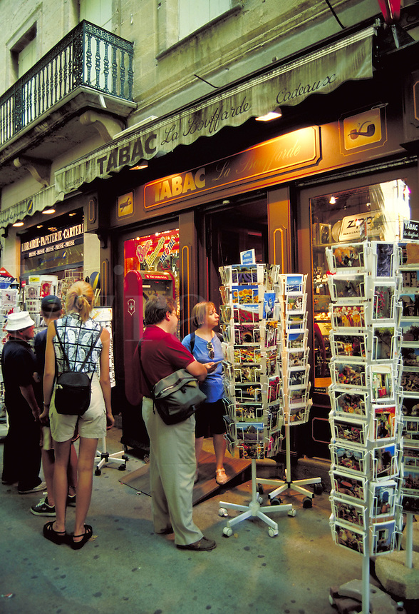 Visitors scan postcards on racks outside tobacco shop. Uzes Provence France.