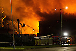 © Joel Goodman . No syndication permitted . 21/08/2013 . Stockport , UK . Firefighters use elevated platforms to tackle a large blaze at the J25 Recycling Centre in Bredbury , Stockport this morning (Wednesday 21st August 2013) where a building and bales of recyclable material are alight . The fire , which started late last night (20th August) is being tackled by more than 50 fire crew . The site , which is adjacent to a branch of Morrisons Supermarket and McDonalds , is off Junction 25 of the M60 motorway , exits for which are closed in both directions . Photo credit : Joel Goodman