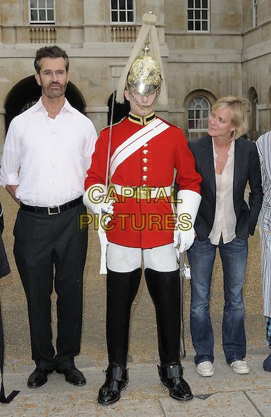 Rupert Everett, trooper, Hermione Norris.The photocall to launch the 8th annual Maggie's London Night Hike, a 10 or 20-mile night walk through central London to raise funds to provide practical, emotional & social support for anyone with cancer, Horse Guards, Whitehall, London, England..August 15th, 2012.full length white blue black guard gold helmet uniform shirt blazer sheer top jeans denim trousers looking staring peeking stubble facial hair.CAP/CAN.©Can Nguyen/Capital Pictures.