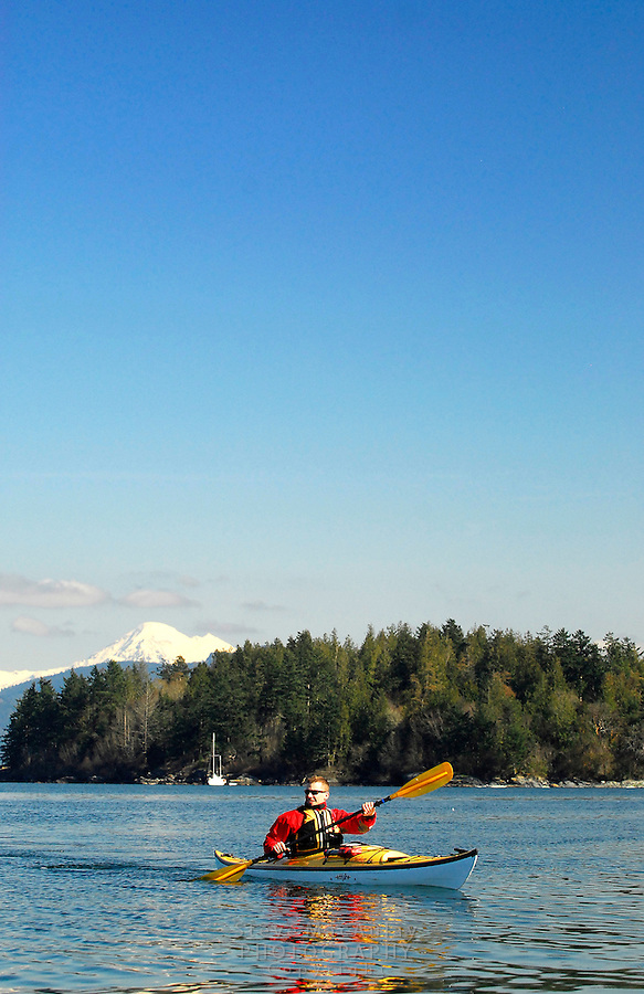 Male paddler in yellow kayak and red PFD paddling in San Juan Islands with Mount Baker visible in background,  San Juan Islands, WA.