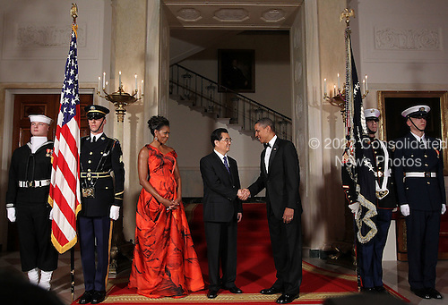 United States President Barack Obama (R) shakes hands with President Hu Jintao of China (C) as first lady Michelle Obama looks on as they pose for the official photo at the Grand Staircase of the White House January 19, 2011 in Washington, DC. Obama is hosting a state dinner for Hu this evening.  .Credit: Alex Wong / Pool via CNP