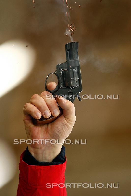 Duitsland, Berlijn. 8 februari 2008 .WK schaatsen allround 2008 .Training  .Een hand haalt de trekker over van een startpistool. Uit de loop van het pistool komen rook en vuur