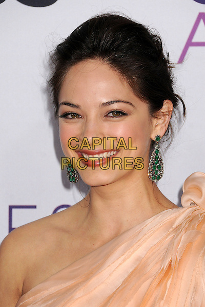 Kristin Kreuk.People's Choice Awards 2013 - Arrivals held at Nokia Theatre L.A. Live, Los Angeles, California, USA..January 9th, 2013.headshot portrait dangling earrings green peach one shoulder top gold smiling .CAP/ADM/BP.©Byron Purvis/AdMedia/Capital Pictures.