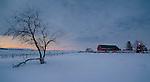 Idaho, South Central, Twin Falls, Filer. Pre-dawn light over a red barn and farm scene in winter.