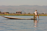 Myanmar, Burma.  Fisherman Laying Out  his Nets, Rowing with One Leg, in the Style Common to Inle Lake, Shan State.