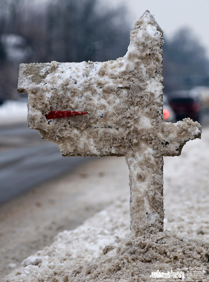 A roadside mailbox is coated with a blanket snow sprayed on it by passing snow plows along State Street near Uptown Westerville during a snow storm.  Photo Copyright Gary Gardiner. Not be used without written permission detailing exact usage.