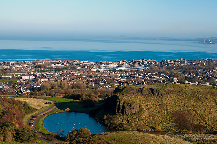 Views towards the East of Edinburgh from Arthur's Seat. The Dunsapie Loch and Dunsapie Craig are in foreground with the district of Portobello and the Firth of Forth in the back. .Dunsapie Loch is one of three lochs located within Holyrood Park (aka Queen's Park)