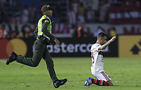 BARRANQUILLA, COLOMBIA - MARCH 04: A Player of Flamengo after defeated as a Police officer runs during the group A Soccer match of Copa CONMEBOL Libertadores between Junior and Flamengo at Estadio Metropolitano on March 4, 2020 in Barranquilla, Colombia. (Photo by Daniel Munoz/VIEW press via Getty Images)
