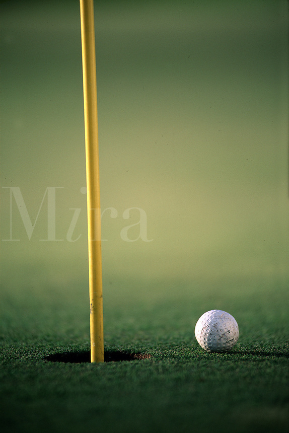 Detail of a golf ball approaching a hole with a flag.