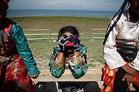 Tibetan children near Qinghai Lake. Qinghai Lake, China's largest inland body of water lies at over 3000m on the Qinghai-Tibetan Plateau. The lake has been shrinking in recent decades, as a result of increased water-usage for local agriculture. Qinghai Province. China. 2010