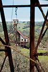 Headframe of the Kennedy Gold Mine in the through the framework of the Argonaut Mine hoist house. Both mines were among California's deepest and riches gold mines until closed during World War II...Snow-capped Crystal Range of the Sierra Nevada at the horizon.