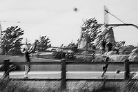 In slow motion black and white, a basketball is captured in midair with the young athlete to the left and the basket and backboard to the right all at a neighborhood park on a spring afternoon.