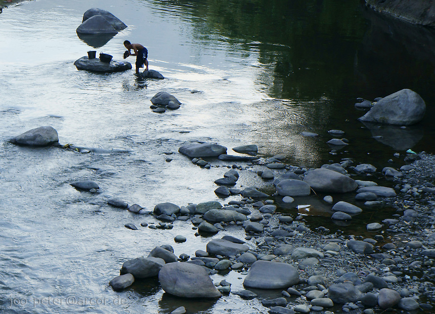 men washing clothes in river leading to coastal city Ende in island  Flores in archipelago of Indonesia