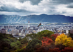 Kyoto tower in city landscape with an eagle flying by and mountains in the background under dramatic stormy sky, autumn city scenery. Higashiyama, Kyoto, Japan 2017.