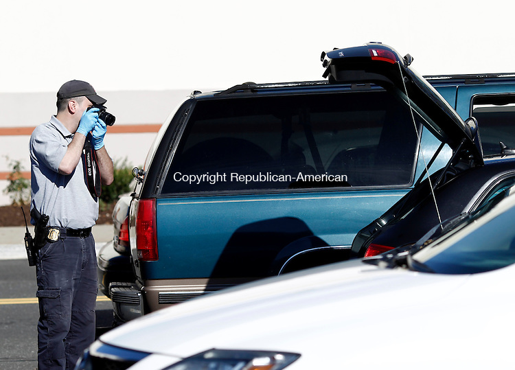 Waterbury, CT- 03 October 2014-100314CM01- A Waterbury police officer takes photographs of an Audi in the parking lot of the Brass Mill Center in Waterbury on Friday.  The vehicle is suspected to be involved in a string of robberies.     Christopher Massa Republican-American