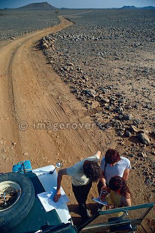 Algeria, Africa, Sahara. Travellers, undertaking a sahara trip in their Series Land Rovers having a navigation stop, while slowly approaching the Hoggar mountains and Assekrem from the north. --- No releases available. Automotive trademarks are the property of the trademark holder, authorization may be needed for some uses.