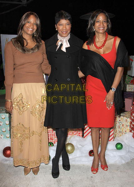 NATALIE COLE & sisters Timolin & Casey.Natalie Cole Lights Capitolís Legendary Rooftop Christmas Tree. Held At Capitol Records Rooftop, Hollywood, California, USA..November 19th, 2009.full length black gold silk satin scarf red dress brown skirt top switch on pink  siblings family brown red .CAP/ADM/KB.©Kevan Brooks/AdMedia/Capital Pictures.